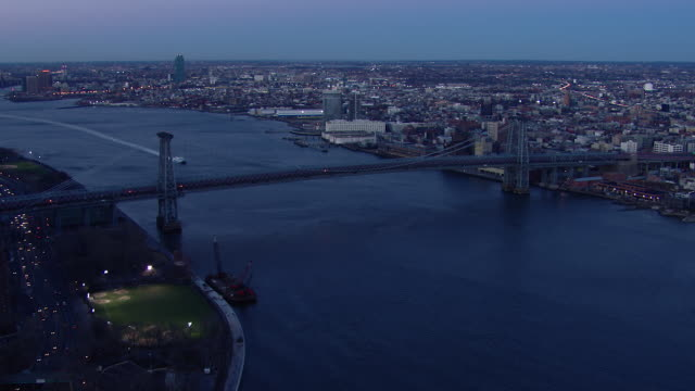 the williamsburg bridge at twilight in new york city. the bridge crosses the east river, connecting manhattan's lower east side to brooklyn's williamsburg neighborhood. - williamsburg bridge stock videos and b-roll footage