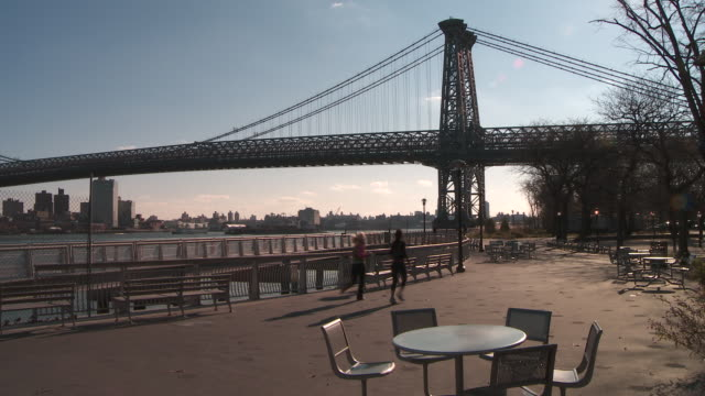 the williamsburg bridge stretching over the east river to brooklyn as joggers run through a manhattan park in the morning - williamsburg bridge stock videos & royalty-free footage