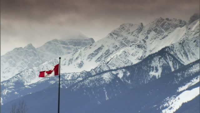 the wind blows a canadian flag in the mountains. - bandiera del canada video stock e b–roll