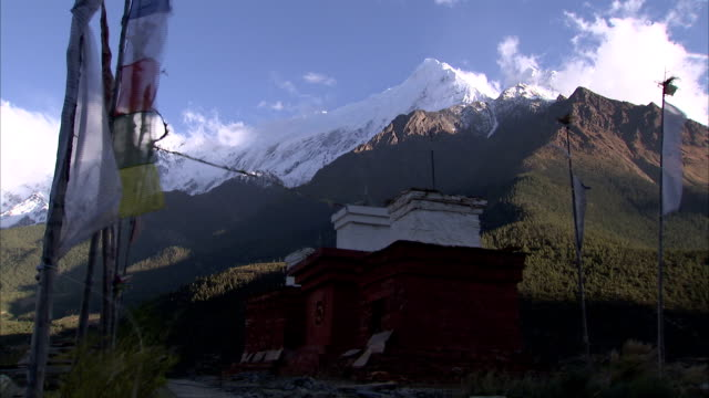 The wind blows through prayer flags in a Nepalese village. Available in HD.