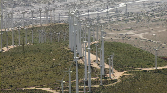 The wind causes turbines to spin on a hilltop.