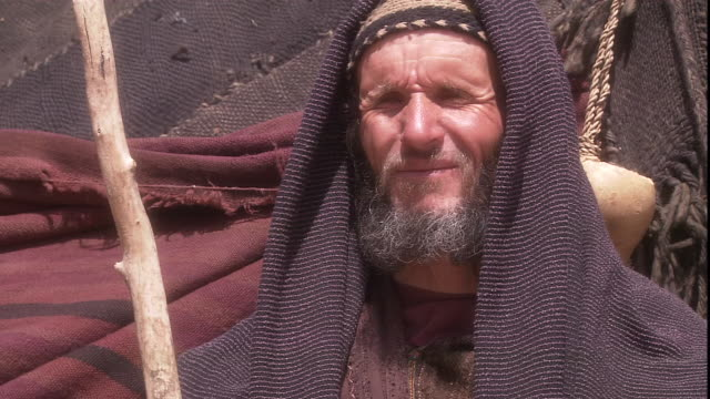 the wind flutters a bearded man's robes as he holds a wooden staff. - nomadic people stock videos & royalty-free footage