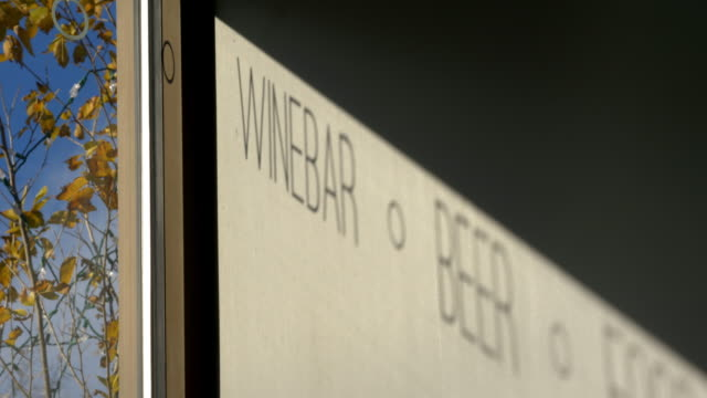 the window sign for wine bar and beer window makes a shadow on the wall - wine bar stock videos & royalty-free footage