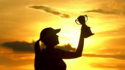 The winner holding a trophy at sunset silhouette