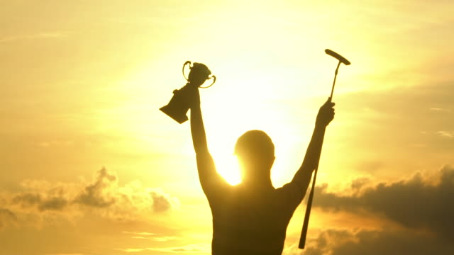 the winner of golf tournament holding trophy at sunset - golf stock videos & royalty-free footage