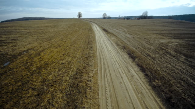 the winter's rural landscape. the dirty country road in the fields. aerial view. - inquadratura dall'ascensore video stock e b–roll