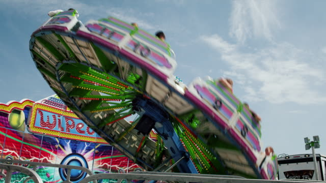 vidéos et rushes de the wipe out attraction ride spins around on the midway at a state fair. - fête foraine