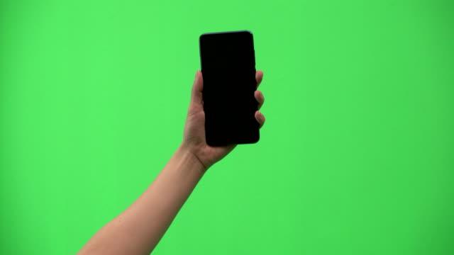 vidéos et rushes de la main de la femme a été en utilisant le téléphone mobile sur fond vert - fond vert