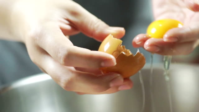 the woman hands separating egg yolk from white for cooking food in the kitchen. - egg yolk stock videos and b-roll footage