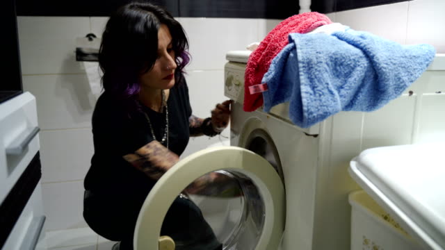 the woman puts the laundry in the washing machine-stay at home mother - tumble dryer stock videos & royalty-free footage
