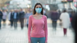 The woman with medical face mask stands in the crowded street. time lapse
