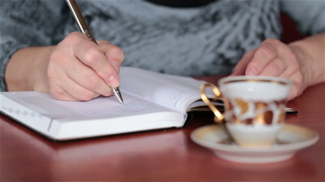 the woman writes in a notebook and drinks coffee. - writer stock videos & royalty-free footage
