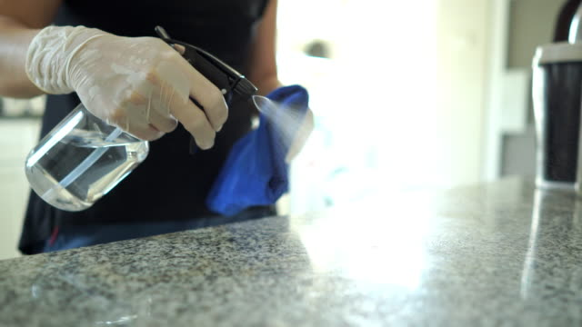 the woman's hand with hand glove using alcohol spray and wiping down surfaces on the table in the kitchen. - dustman stock videos & royalty-free footage