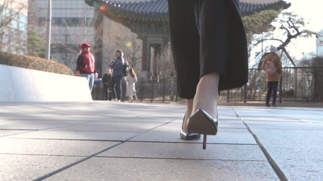 vídeos y material grabado en eventos de stock de the woman's leg and walking on the street in the city buildings - pie humano