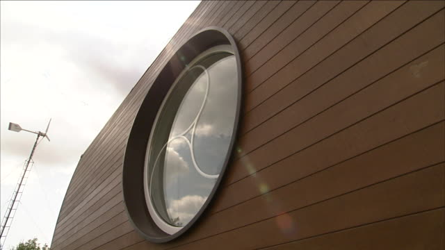 the wood siding of a home features a round window etched with a design. - 操車場点の映像素材/bロール