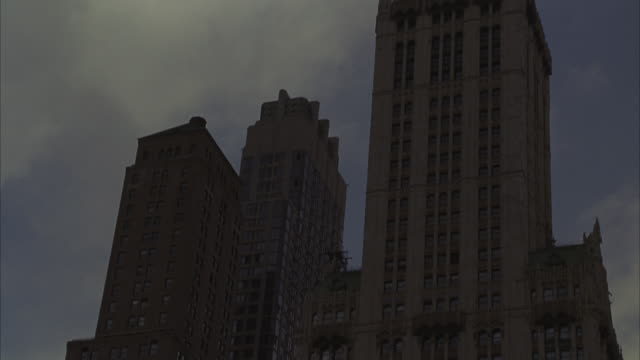 the woolworth building towers into a cloudy sky in new york city. - woolworth building stock videos & royalty-free footage