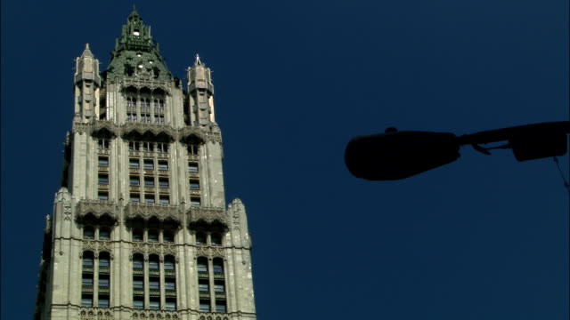 the woolworth building towers over a street lamp in new york city. - woolworth building stock videos & royalty-free footage