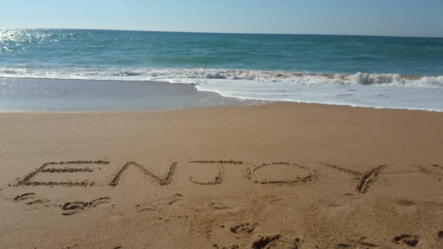 """vídeos de stock, filmes e b-roll de the word """"enjoy"""" written in the sand - escrita ocidental"""