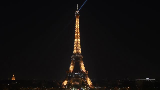 the word 'merci' is projected on the eiffel tower to honor all personnel contributing to the effort to combat the new type of coronavirus pandemic,... - eiffel tower paris stock videos & royalty-free footage
