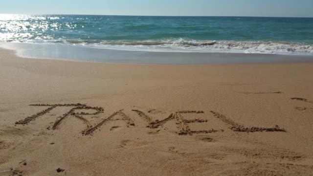 """the word """"travel"""" written in the sand - västerländsk text bildbanksvideor och videomaterial från bakom kulisserna"""