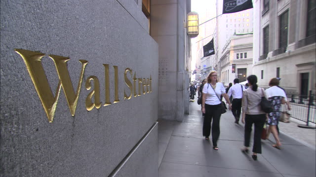 ws the words 'wall street' etched in side of building with commuters walking by / new york city, new york, usa   - wall street video stock e b–roll