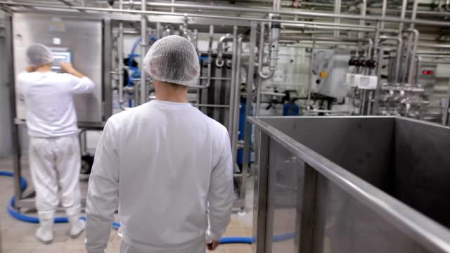 vídeos y material grabado en eventos de stock de el trabajador entra a trabajar en la fábrica de alimentos - leche