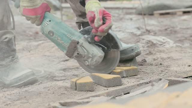 vídeos y material grabado en eventos de stock de el trabajador corta los adoquines en dos. hace un sendero en el patio de la casa. - miembro humano