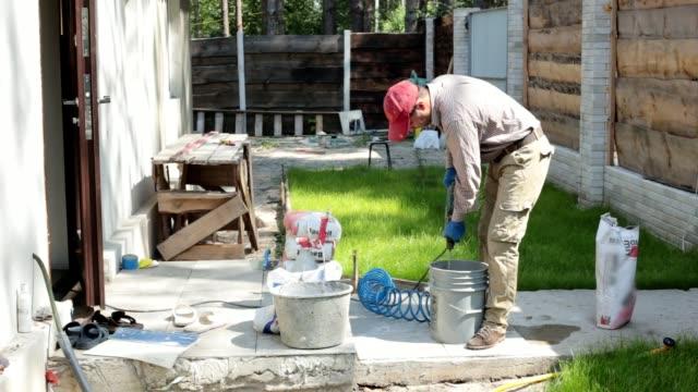 die arbeitskraft mischt zement und wasser für gipser-arbeiten. - zement stock-videos und b-roll-filmmaterial