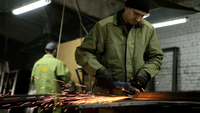 The worker polishes the welded seams on the metal workpiece.