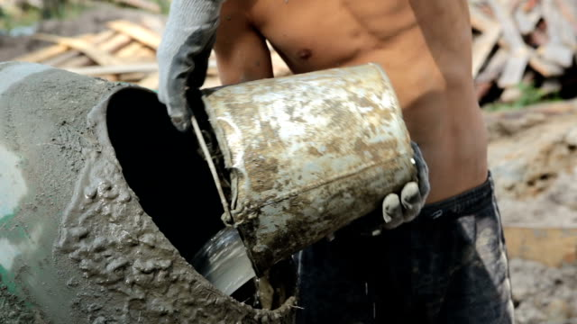 the worker pours water into the concrete mixer. - cement mixer stock videos and b-roll footage
