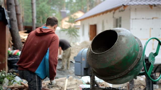 The worker prepares a concrete mix in a concrete mixer.
