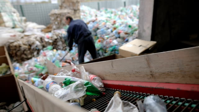 the worker pushes plastic bottles with a shovel for recycling.working at a recycling factory - plastic stock videos & royalty-free footage