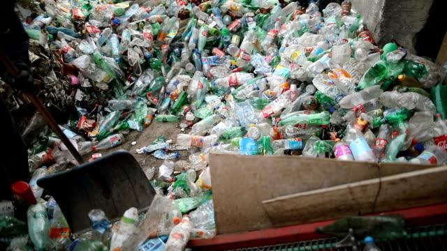 Der Arbeiter schiebt Plastikflaschen mit einer Schaufel zum Recycling. Arbeiten in einer Recyclingfabrik