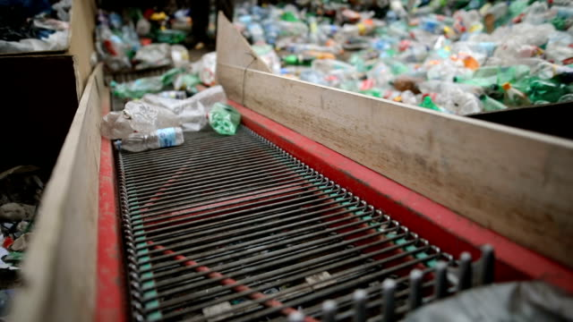 the worker pushes plastic bottles with a shovel for recycling.working at a recycling factory - belt stock videos & royalty-free footage