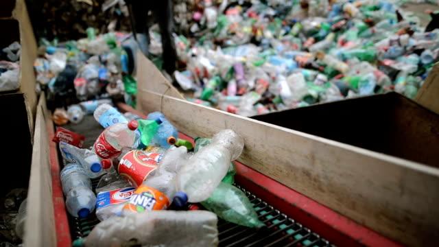 労働者は、リサイクルのためにシャベルでペットボトルをプッシュします。リサイクル工場で働く - リサイクル工場点の映像素材/bロール