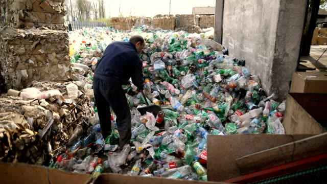 the worker pushes plastic bottles with a shovel for recycling.working at a recycling factory - ease stock videos & royalty-free footage