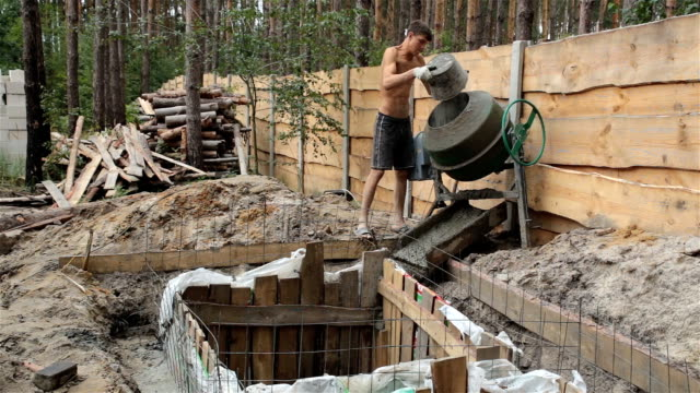 the worker puts the cement in the concrete mixer. - cement mixer stock videos & royalty-free footage