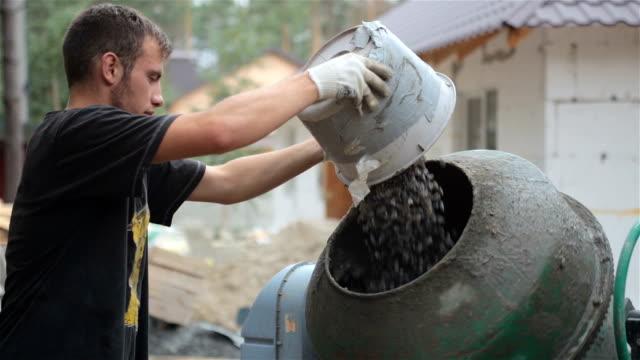 労働者は、コンクリート ミキサーに砂利を入れます。
