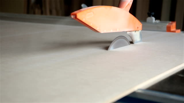 the worker saws the wooden sheets by a circular saw. - hand saw stock videos and b-roll footage