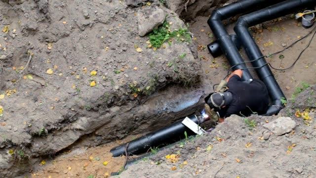 the worker welds the joint of the pipeline. - plumber stock videos and b-roll footage