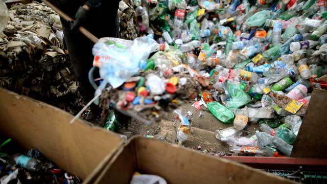シャベルを持つ労働者は、リサイクルのために廃棄物を分類します。リサイクル工場で働く - リサイクル工場点の映像素材/bロール