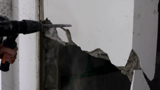 vídeos de stock, filmes e b-roll de os trabalhadores desmantelou a parede interna do edifício com uma picareta - excitação