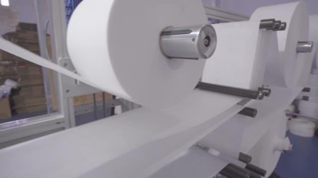 die funktionierende produktionslinie der maskenfabrik - textilien stock-videos und b-roll-filmmaterial
