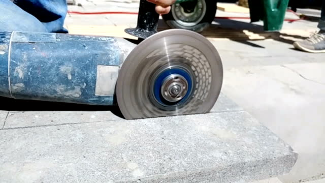 the workman cutting concrete blocks by diamond circular saw blade. - stone material stock videos & royalty-free footage