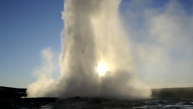 the world famous geysir's strokkur geyser erupting backlit at sunrise. iceland. - geyser stock videos and b-roll footage