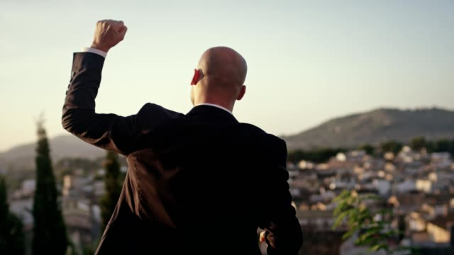 the world is mine. businessman celebrating success - podio video stock e b–roll