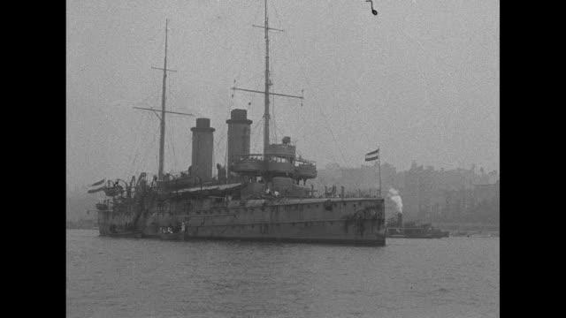 WS the World War I Dutch training cruiser Zeeland as it cruises past New York City / pan along length of Zeeland / artillery gun rotates on deck /...