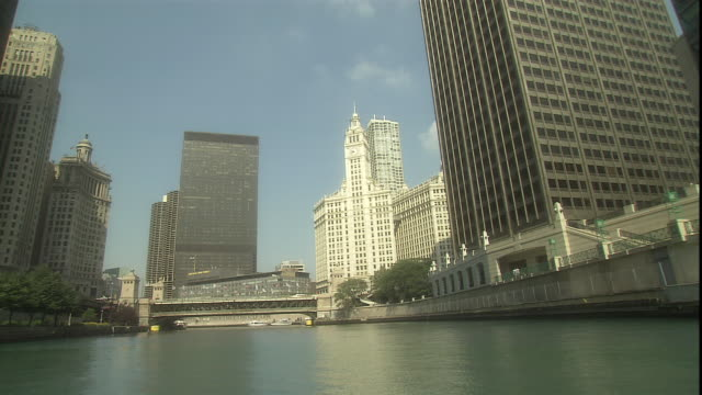 the wrigley building towers above the chicago river. - レガッタリグレービル点の映像素材/bロール