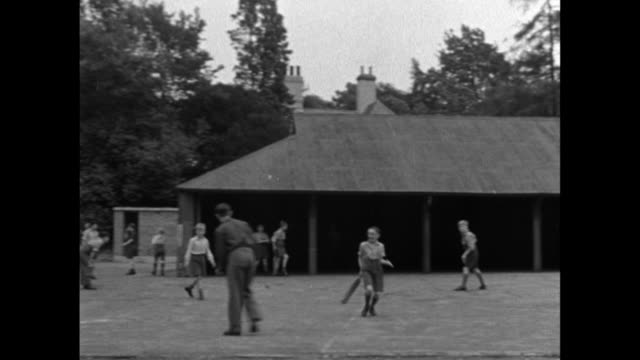pan the yard of marylands orphanage where children are playing and exercising / united kingdom - 1950年点の映像素材/bロール