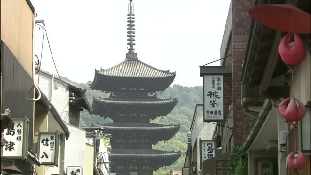 the yasaka pagoda overlooks a shop-lined street in kyoto, japan. - kyoto temple stock videos and b-roll footage